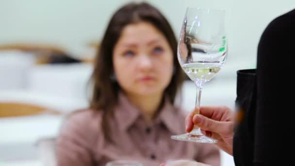 detail z ženské sommelier držení sklenice s bílým vínem na Košt vína