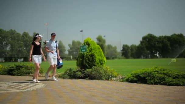 Junger Mann und Frau auf grünem Gras im Golfclub