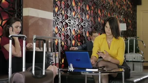 businesswomen working with laptop and using phone on sofa