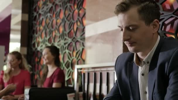 close-up of business man using laptop with women on background