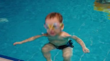 Boy in goggles swimming in pool.