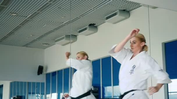 blonde Frau in weißem Karategi
