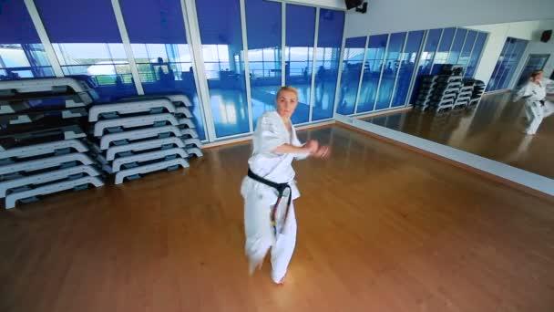 žena cvičí karate v tělocvičně