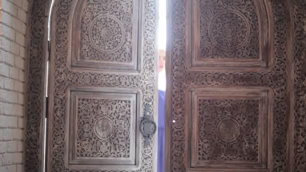 mladá blond žena v purpurové šaty otevřené dveře a vstoupit do starobylé budově