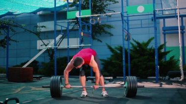 Man with Barbell in outdoor gym