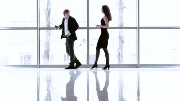 két fiatal üzletemberek a modern bemutatóterem, nagy ablakok fekete öltöny