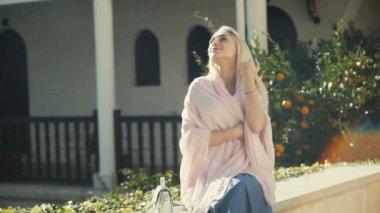 Blonde woman sitting on bench in garden