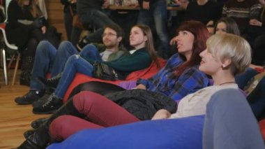 Young people watching comic performance and smile. Men and women sitting on the floor on the pillows.
