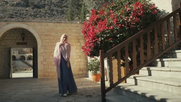 The camera focuses on stone stairs and bush with red flowers. Beautiful blonde in pink headscarf and long dress goes to the stairs. Smiling woman holding right hand by headscarf. She's going upstairs.