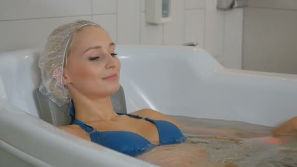 Krásná žena v bikinách a sprchový cap, kterým v bílé vaně a relaxační. Atraktivní žena užívat hydromasážní s bublinami v lázni. Postupy hydromasážní