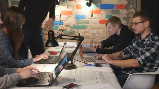 Lidé sedí u stolu a práci na přenosných počítačů v kanceláři. obchodní lidé dokončit svá díla. Fotoaparát zaostří na prázdné pracovní notebooky
