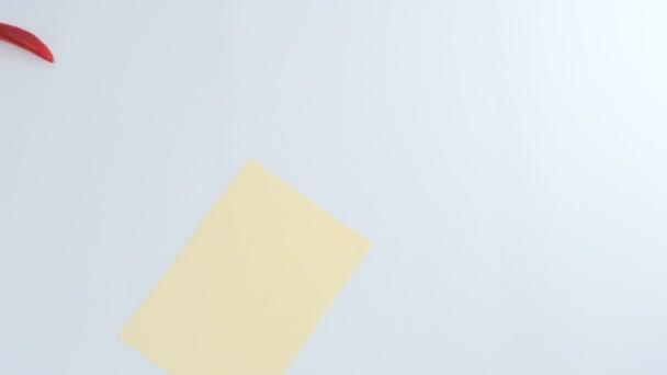 Fotoaparát zaostřuje na bílém pozadí. Žlutý cár papíru z levé strany. Červené ozdobné papričky se pohybuje kolem prázdný list. Papriky se pohybují v poznámce v centru výstřel a obklopují jej
