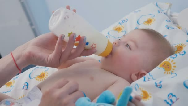 Close-up. Portrait of little boy is laying on the nappy. Adorable baby sucks the mixture from kids bottle. Mothers hand hold a bottle. Cute little boy is eating the food fusion for kids.