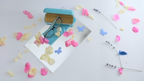 A szemüvegek és szemüveggel is, többek között a rózsaszirom, a dekoratív pillangók és a szárított virágok, kis gallyakból fehér alapon. Fehér kártya kívánságait és rózsaszirom jelenik meg a képernyőn. A díszítő toll és rózsaszirom elszáll