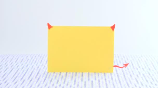 Egy sárga papír sablon formájában ördög szarvak és a farok áll, pontokkal tagolt háttér előtt. A trident, toll, hogy mozog a jobb oldalon. A piros fether elszáll, és a trident a sárga sablon.