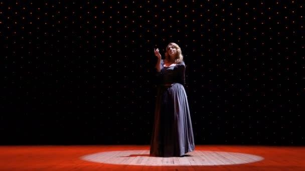 schöne Frau im langen Kleid im Scheinwerferlicht