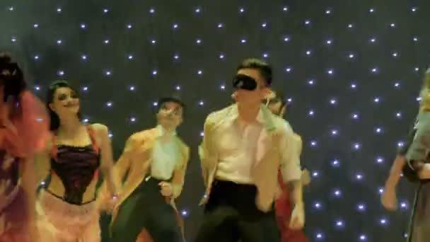 Emberek festői jelmezek táncol és énekel a színpadon, a modern Színház
