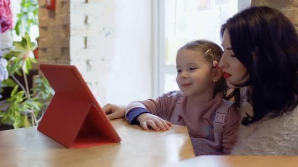 Mutter und kleine Tochter gucken Cartoons und warten im Café auf ihre Bestellung