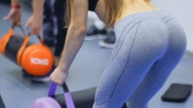 Woman makes exercise for buttocks with weight in the gym