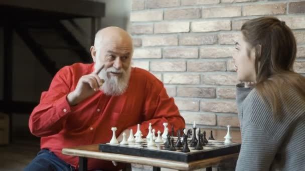 Großvater bringt Enkelin beim Schachspiel Strategie bei