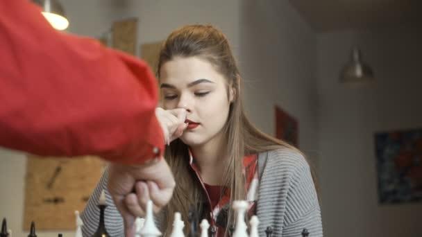 junges Mädchen spielt Schach mit Großvater