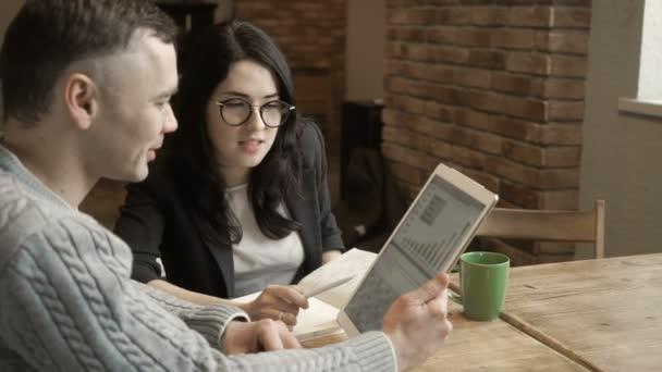 Junger Mann spricht mit Frau beim Blick auf digitales Tablet