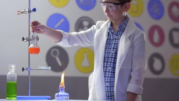 Školák se mísí oranžová kapalina v baňce v laboratoři