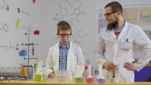 Ragazzo sorpreso esamina fumante boccette in laboratorio