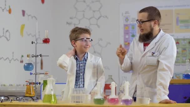 Assistente di laboratorio e il suo allievo Guarda fumanti boccette in laboratorio