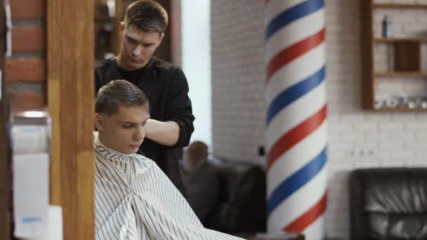 Professional barber makes hairstyle with electric razor to a young man