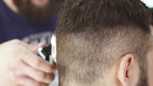 Profesionální kadeřnice dělá účes s elektrický holicí strojek klientovi v holičství
