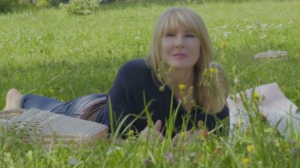 Mladá šťastná žena relaxaci na dece v parku a vlny ruce