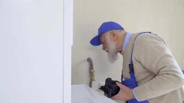 Senior eisgrauer Mann tragen Overalls Reparaturen Kessel ...