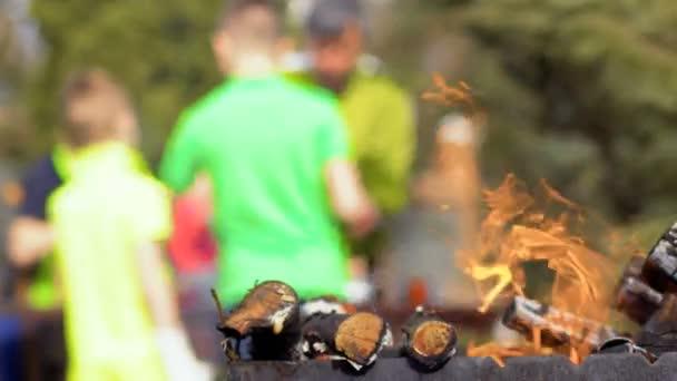 Otec připravuje barbecue se syny na rozostřeného pozadí táborák