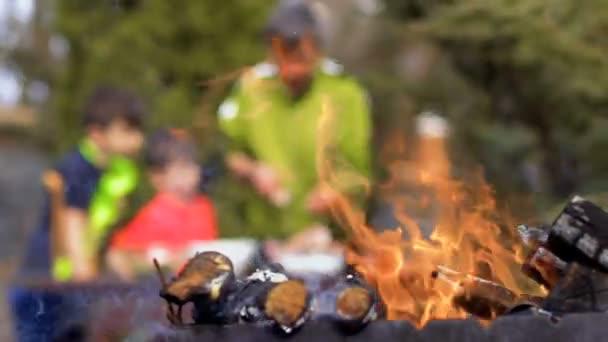 Otec a synové grilování kuchaři u rozostřeného pozadí táborák