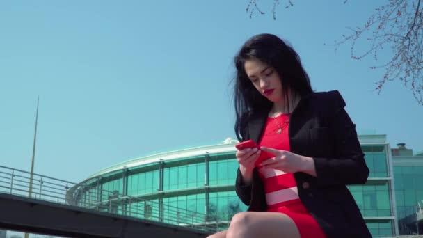 Schöne elegante Frau im roten Kleid mit Telefon im Business-Center-Hintergrund