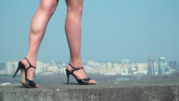 Thin female legs wearing shoes on heels is walking at blurred city background
