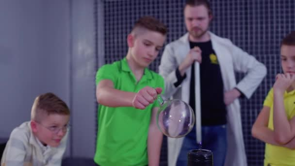 Kinder halten Glaskugel über Tesla-Spule