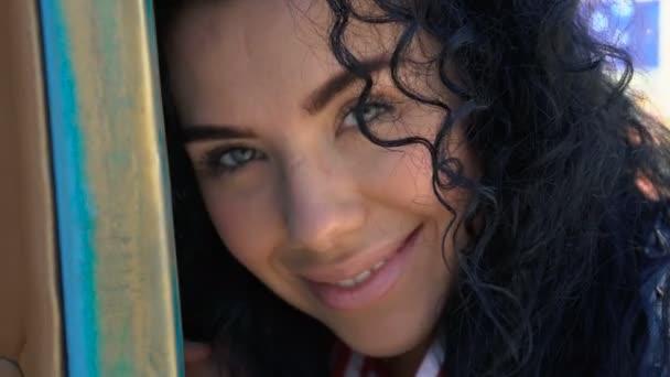 Krásná usmívající se kudrnatá brunetka se zelenýma očima