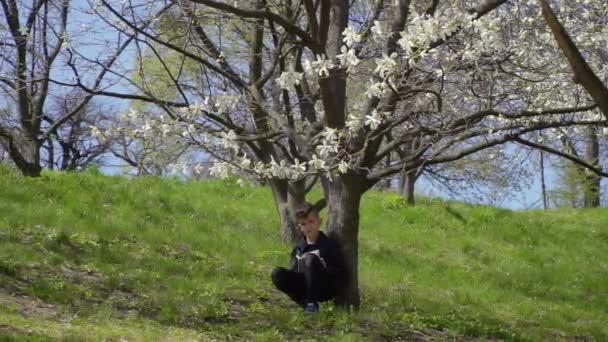 Teenager sits under tree and writes poem