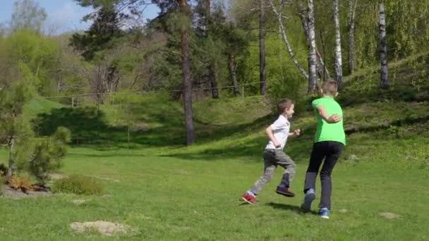 Dva chlapci hraje catch-up v letním parku