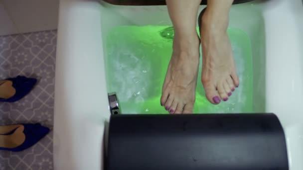 Žena uvolňující nohy zůstávaly v malé lázně s bublinkami a barevná světla