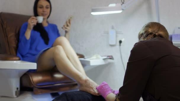 Giovane donna che si distende nel salone di bellezza durante la procedura di pedicure