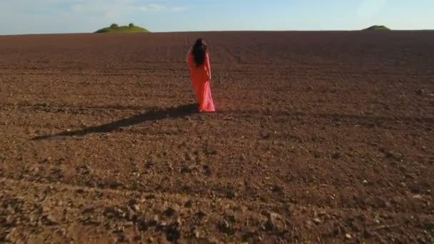 Girl in long red dress walk through plowed field