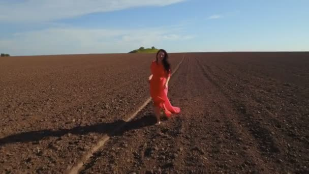 Happy beautiful woman in red dress running through plowed field