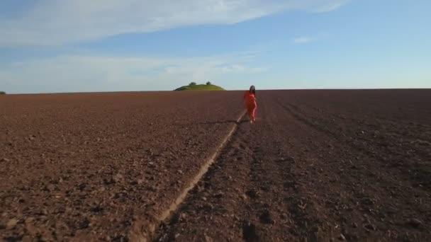 Beautiful brunette wearing long red dress walk at plowed field