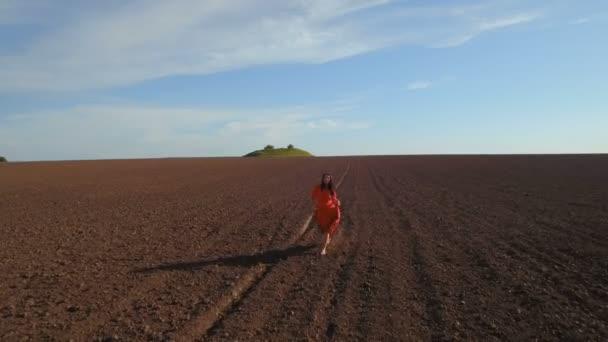 Charming brunette wearing long red dress walking at plowed field
