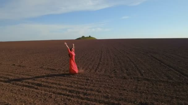Young carefree woman in red dress turning around standing at plowed field