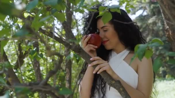Charming woman with red apple enjoy a smell of fruit and smiles to camera