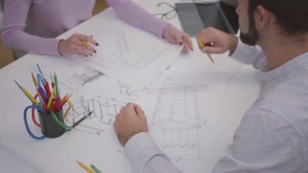 Draufsicht eines männlichen kaukasischen Designers, der sein Projekt mit Kollegen diskutiert und Entwürfe festlegt. zwei junge Architekten, die im Büro arbeiten. Profis, die Ideen ins Leben umsetzen.